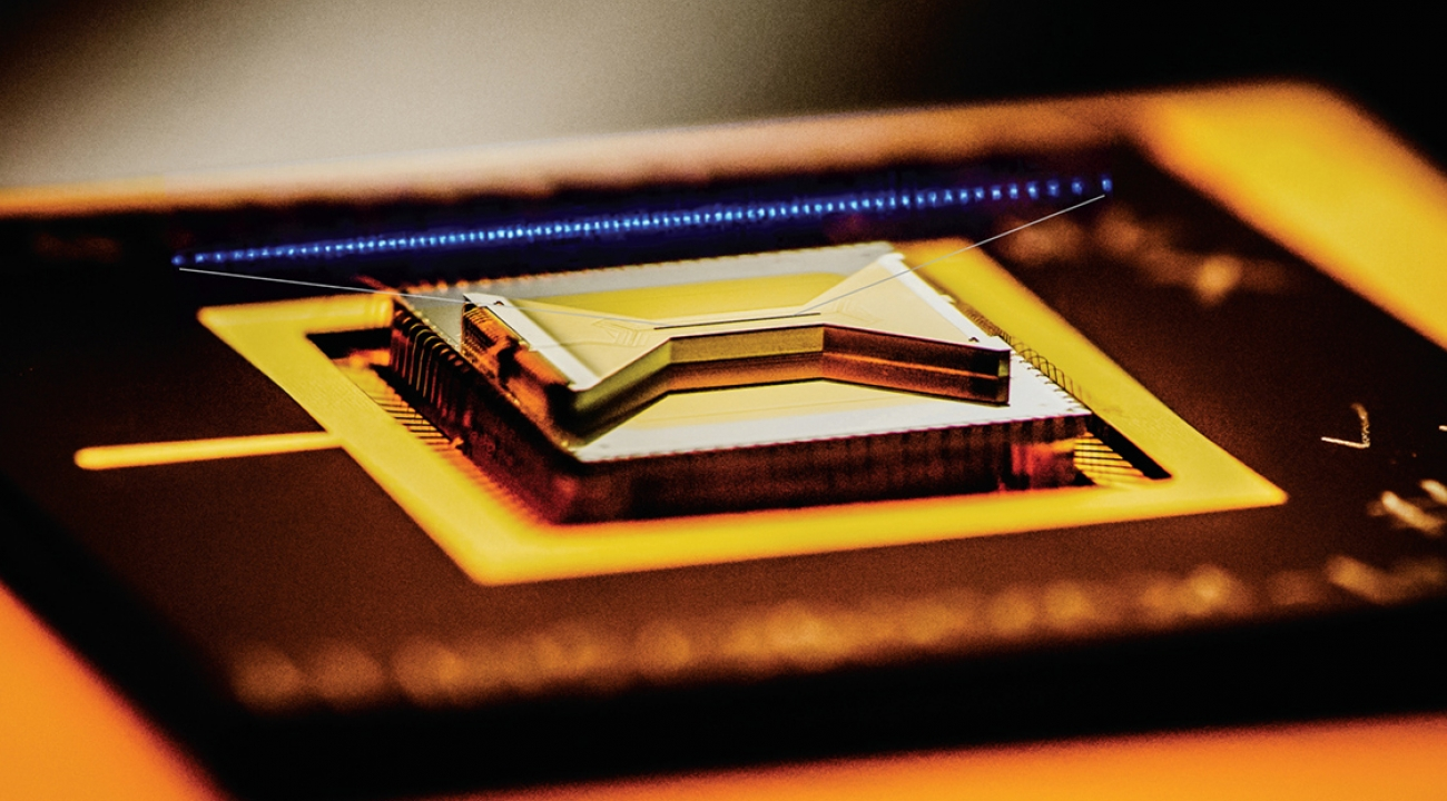 A semiconductor chip ion trap, fabricated by Sandia National Laboratories and used in research at the University of Maryland, composed of gold-plated electrodes that suspend individual atomic ion qubits above the surface of the bow-tie shaped chip. (Credit: Chris Monroe)