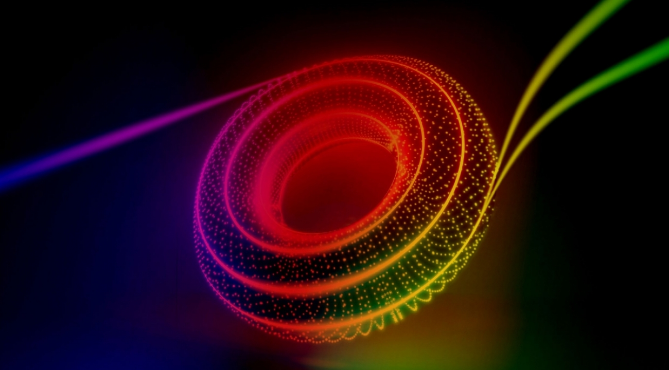 A new technique sees two distinct particles of light enter a chip and two identical twin particles of light leave it. The image artistically combines the journey of twin particles of light along the outer edge of a checkerboard of rings with the abstract shape of its topological underpinnings. (Credit: Kaveh Haerian)
